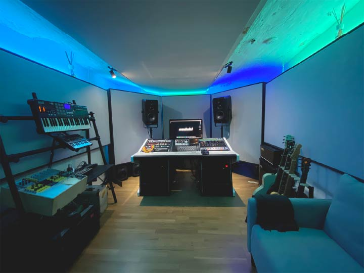 Nadoki studio, at Riverside Studios (Berlin), being lit by blue light. On the left, there is a stand with MIDI keyboards and synthesizers. In the middle, there's a black office chair facing a black studio desk equipped with a computer screen, outboard gear, and two pairs of speakers. On the right, there are two guitars on a stand and a guitar amplifier. The studio walls and ceiling are full of acoustic panels.