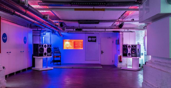 The Lab, at Riverside Studios (Berlin), being lit by blue and red lights. The ceiling is full of pipes and cables, there's a a collumn on the right and, on the back, there's a pair of big speakers and a door. Most of the room is empty.